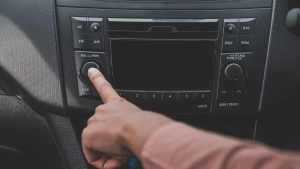 Woman hand turn on the radio on car for listening to music.a